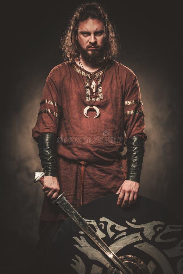 Gniewny Viking z kordzikiem w wojownika tradycyjnych ubraniach, pozuje na ciemnym tle obraz royalty free