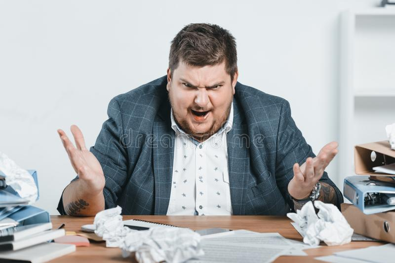 gniewny z nadwagą biznesmen w kostiumu pracuje z dokumentami zdjęcie stock