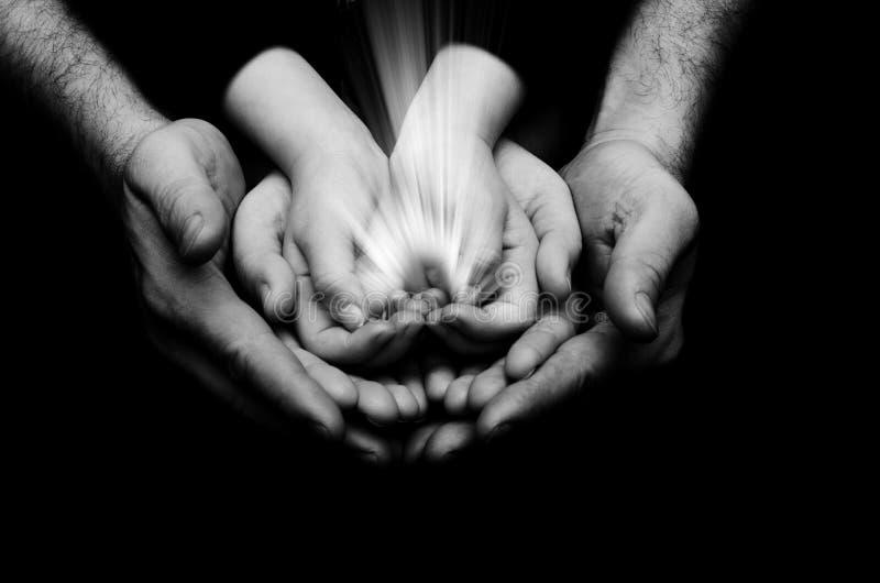 Gnistan av hopp i ett barn räcker whinnehavet vid bakgrund för förälderhandsonmörker Ljuset av tro royaltyfria foton
