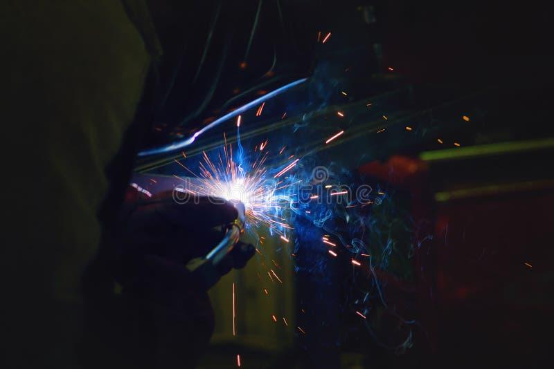 Gnistor under svetsning på produktionsprocessen i halvautomatisk svetsning av metall i skyddande gaser för argon royaltyfria foton