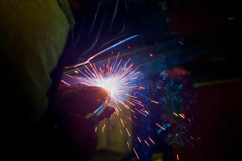 Gnistor under svetsning på produktionsprocessen i halvautomatisk svetsning av metall i skyddande gaser för argon royaltyfri bild