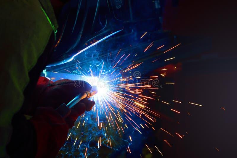 Gnistor under svetsning på produktionsprocessen i halvautomatisk svetsning av metall i skyddande gaser för argon royaltyfri foto