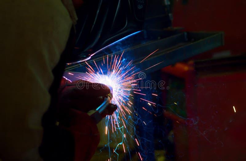 Gnistor under svetsning på produktionsprocessen i halvautomatisk svetsning av metall i skyddande gaser för argon arkivfoto