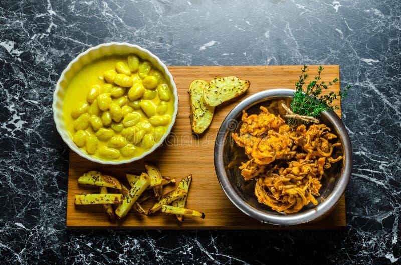 Gnocchi κάρρυ με τα bhajjis και την ψημένη πατάτα στοκ εικόνες