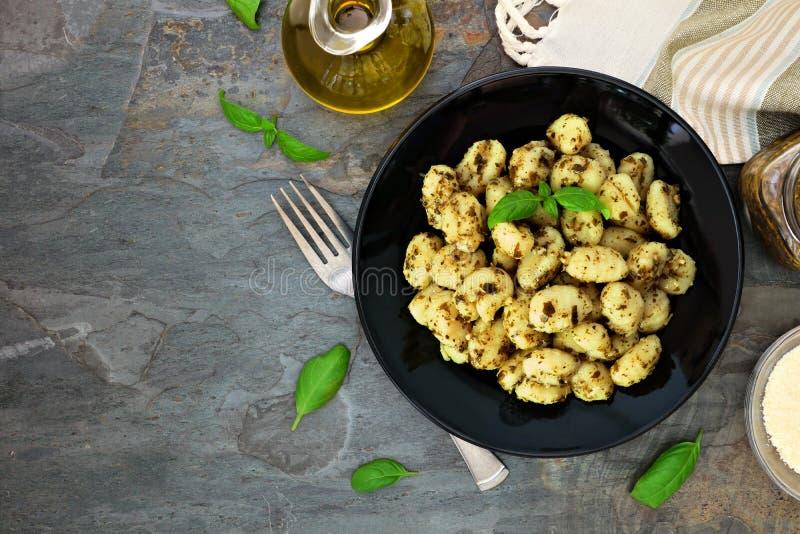Gnocchi με τη σάλτσα pesto, τοπ σκηνή άποψης πέρα από τη σκοτεινή πέτρα στοκ εικόνες