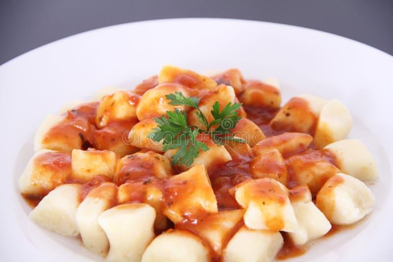 Gnocchi con el sao negro aislado salsa Paulo Brazil del fondo del tomatoe foto de archivo