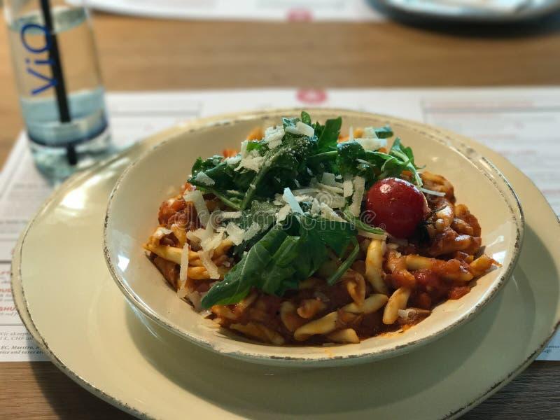 Gnocchi con la salsa de tomate, el queso parmesano, el tomate de cereza y el perejil foto de archivo