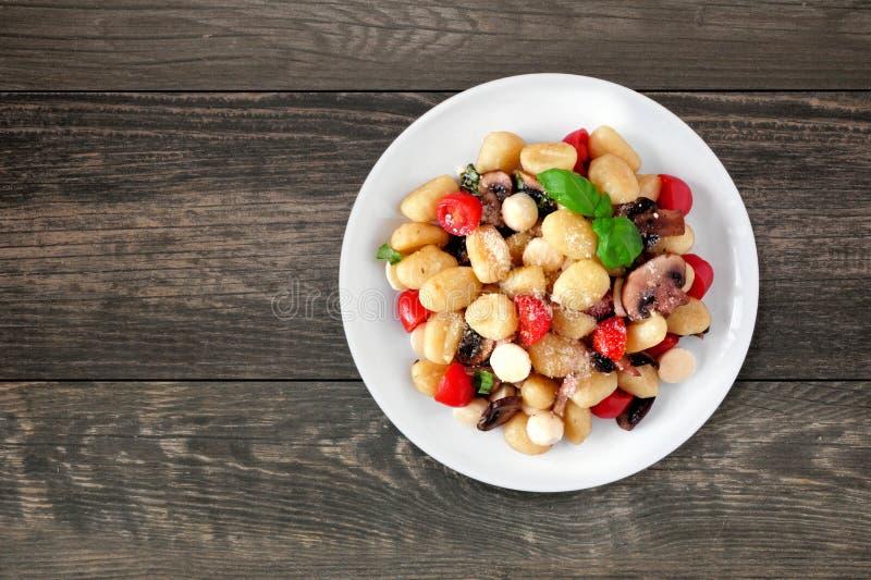 Gnocchi con los tomates, la mozzarella, las setas y la albahaca, visión superior sobre la madera oscura fotografía de archivo