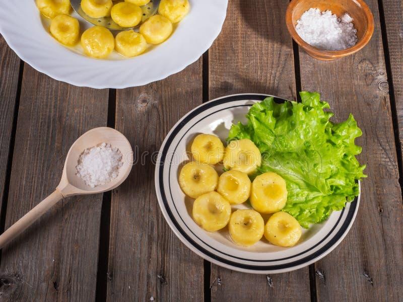 Gnocchi della patata su due piatti, foglie della lattuga di foglia fresca sui piatti leggeri su una vecchia tavola della plancia  immagine stock