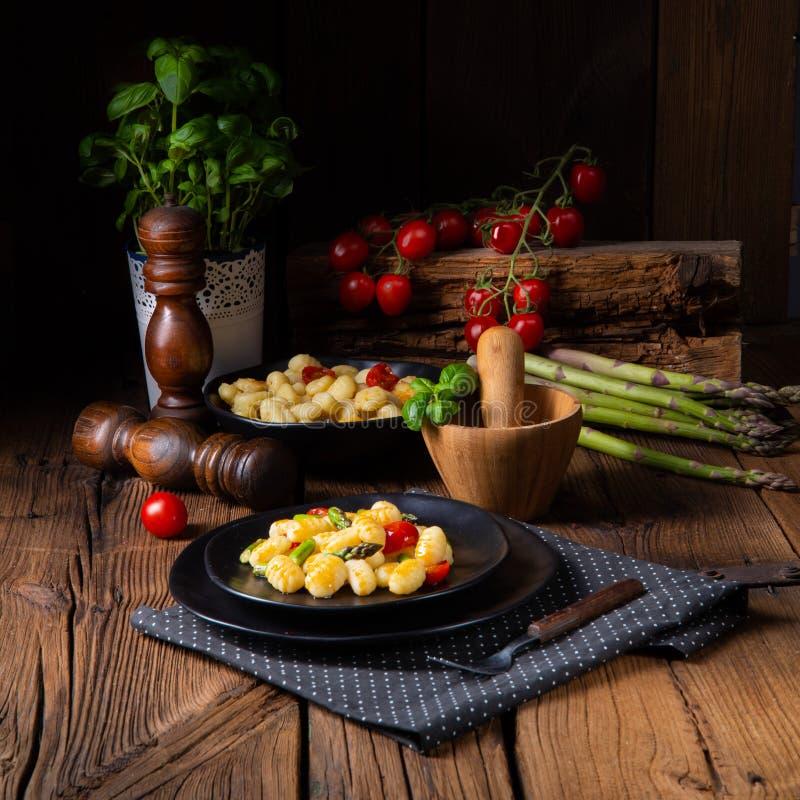 Gnocchi friável com aspargo e os tomates roasted foto de stock