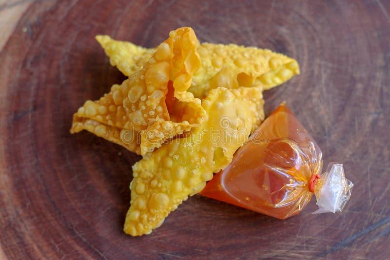 Gnocchi fritti, alimento cinese con salsa nel sacchetto di plastica sulla tavola di legno immagine stock