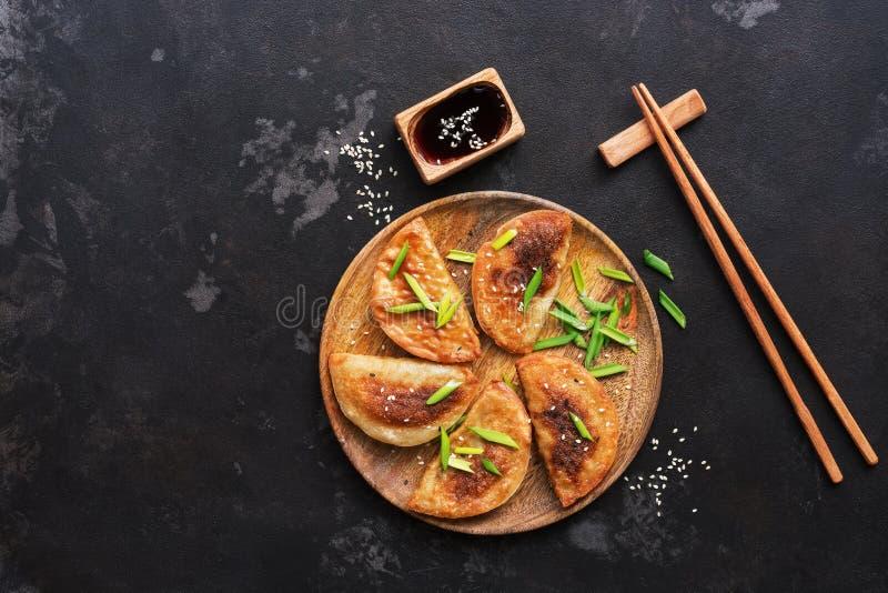 Gnocchi fritti asiatici casalinghi con la erba cipollina, la salsa di soia ed i bastoncini su un fondo di pietra nero Alimento gi fotografia stock