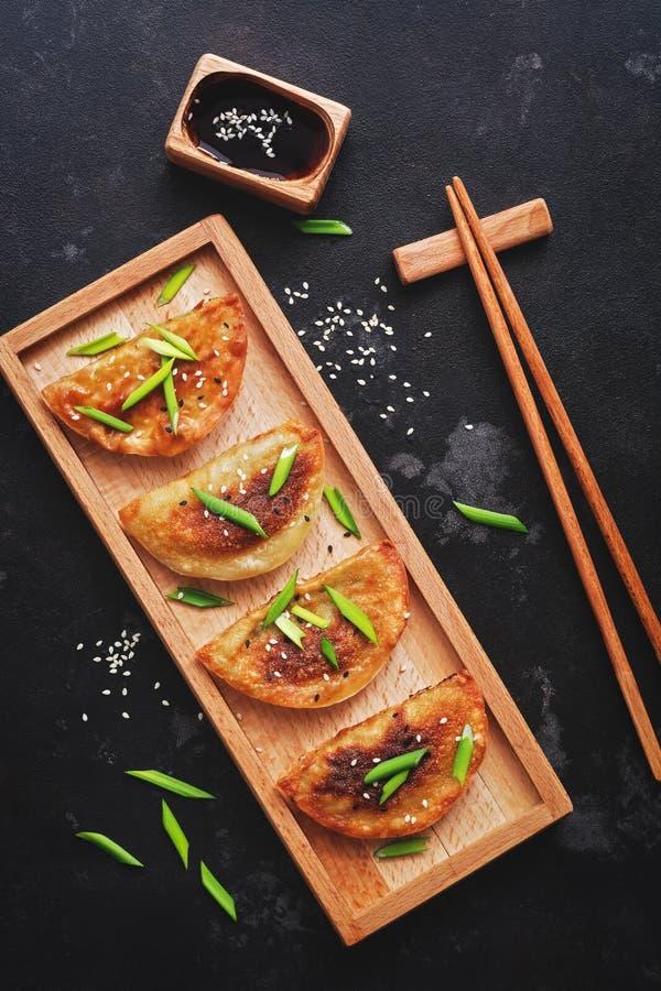 Gnocchi fritti asiatici con le cipolle verdi ed il sesamo, salsa di soia, bastoncini Fondo di pietra nero, vista superiore, dispo immagini stock libere da diritti