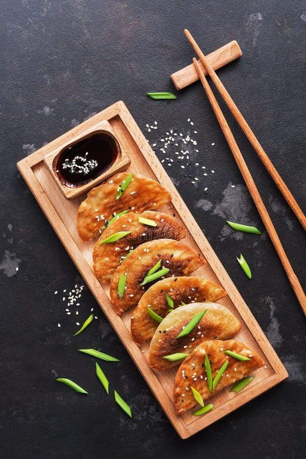 Gnocchi fritti asiatici con le cipolle verdi, salsa di soia, bastoncini su un fondo di pietra nero Vista superiore, disposizione  immagine stock