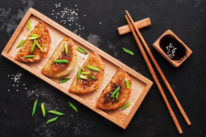 Gnocchi fritti asiatici con le cipolle verdi, salsa di soia, bastoncini su un fondo di pietra nero Vista superiore, disposizione  fotografia stock libera da diritti