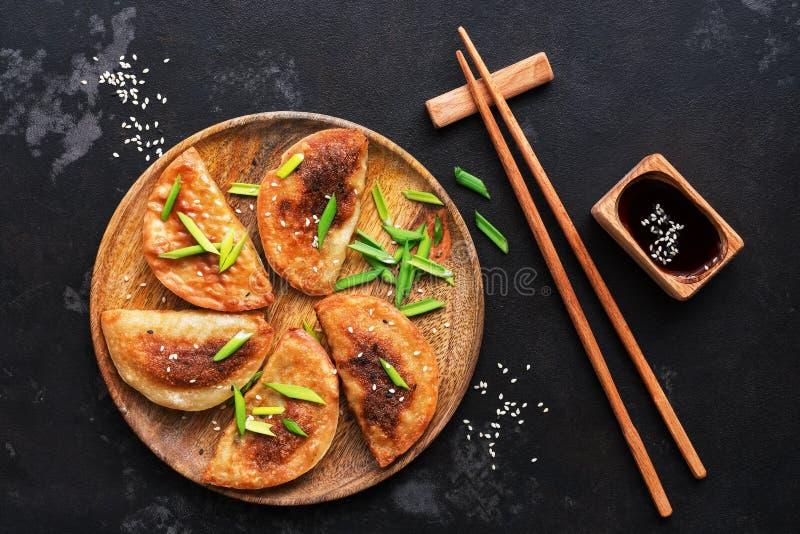 Gnocchi fritti casalinghi con la erba cipollina, la salsa di soia ed i bastoncini su un fondo di pietra nero Alimento asiatico Vi fotografie stock