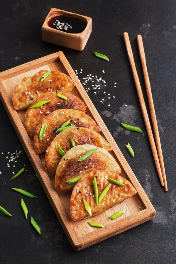Gnocchi fritti casalinghi dell'alimento asiatico su un fondo scuro Gnocchi coreani Fuoco selettivo immagini stock libere da diritti