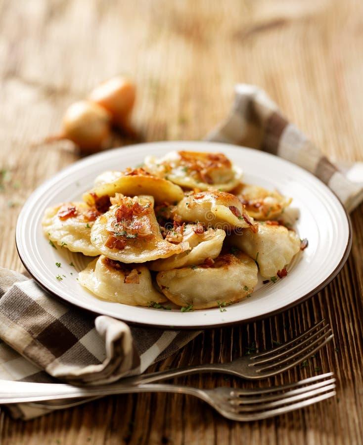 Gnocchi fritti farciti con cavolo e carne spruzzati con i ciccioli del bacon ed il prezzemolo tagliato su un piatto bianco fotografie stock libere da diritti
