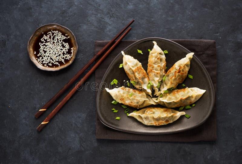 Gnocchi fritti Gyoza in piatto, salsa di soia e bastoncini fotografia stock libera da diritti