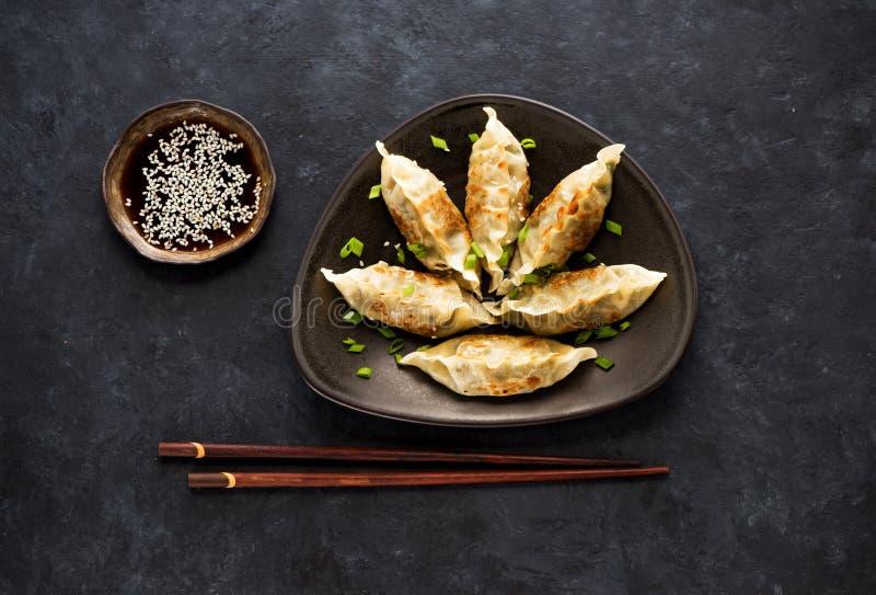 Gnocchi fritti Gyoza su un piatto, su una salsa di soia e sui bastoncini fotografia stock