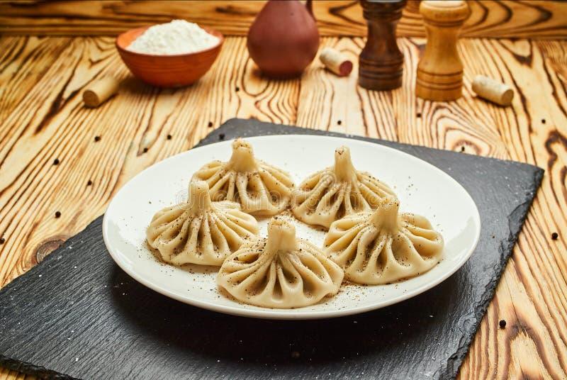 Gnocchi georgiani Khinkali con carne, verdi e la salsa piccante Satsebeli del pomodoro sul piatto bianco immagine stock libera da diritti