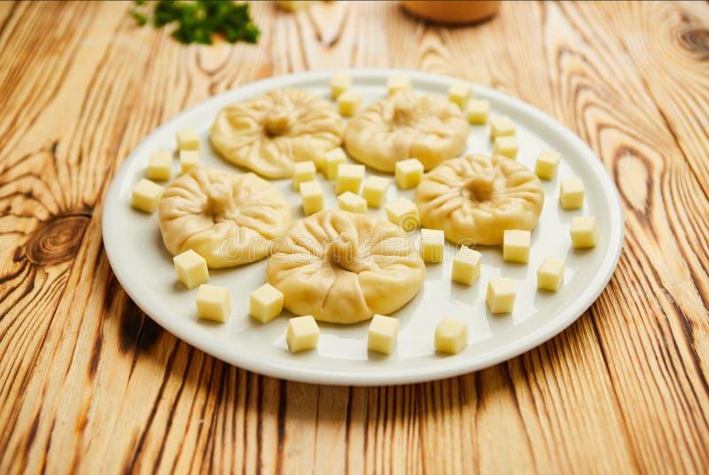 Gnocchi georgiani Khinkali con formaggio, verdi e la salsa piccante Satsebeli del pomodoro sul piatto bianco immagine stock