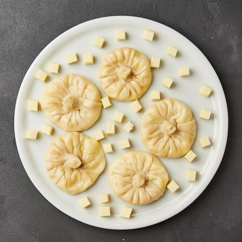 Gnocchi georgiani Khinkali con formaggio, verdi e la salsa piccante Satsebeli del pomodoro sul piatto bianco fotografie stock