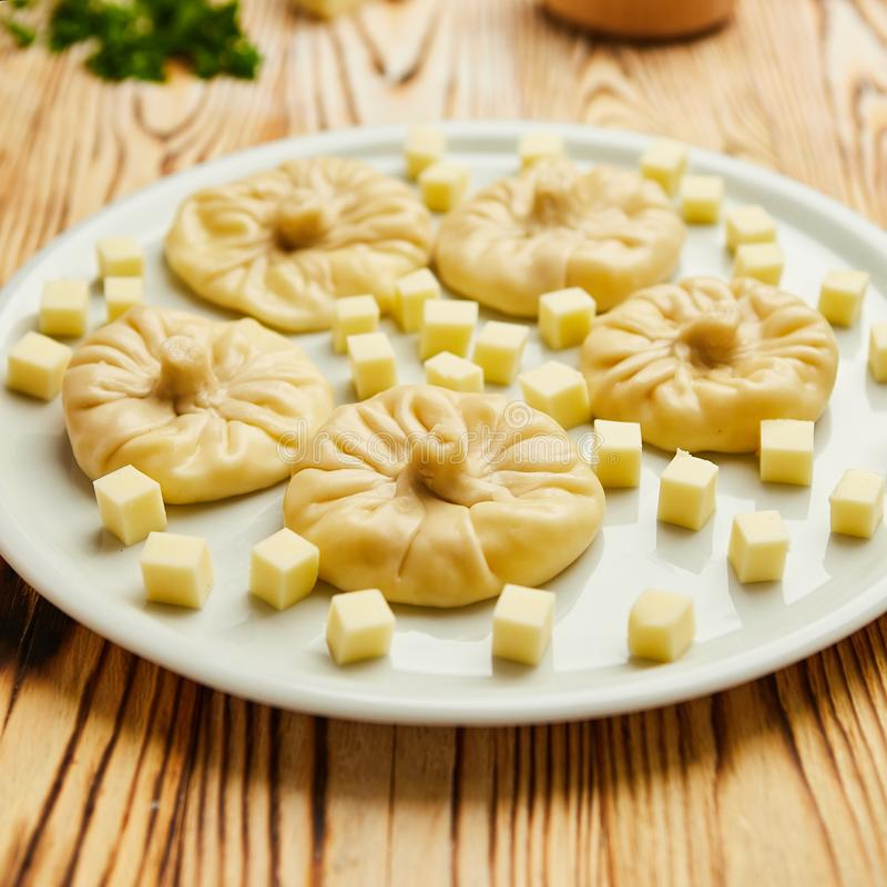 Gnocchi georgiani Khinkali con formaggio, verdi e la salsa piccante Satsebeli del pomodoro sul piatto bianco fotografia stock libera da diritti