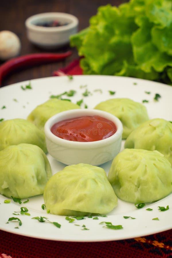 Gnocchi georgiani Khinkali della pasta degli spinaci con il satsebeli piccante della salsa del pomodoro e della carne Priorità ba fotografia stock