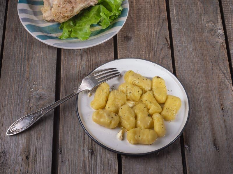 Gnocchi hervido de la patata en una placa de cerámica ligera, en el fondo una placa con el pollo y la ensalada foto de archivo libre de regalías