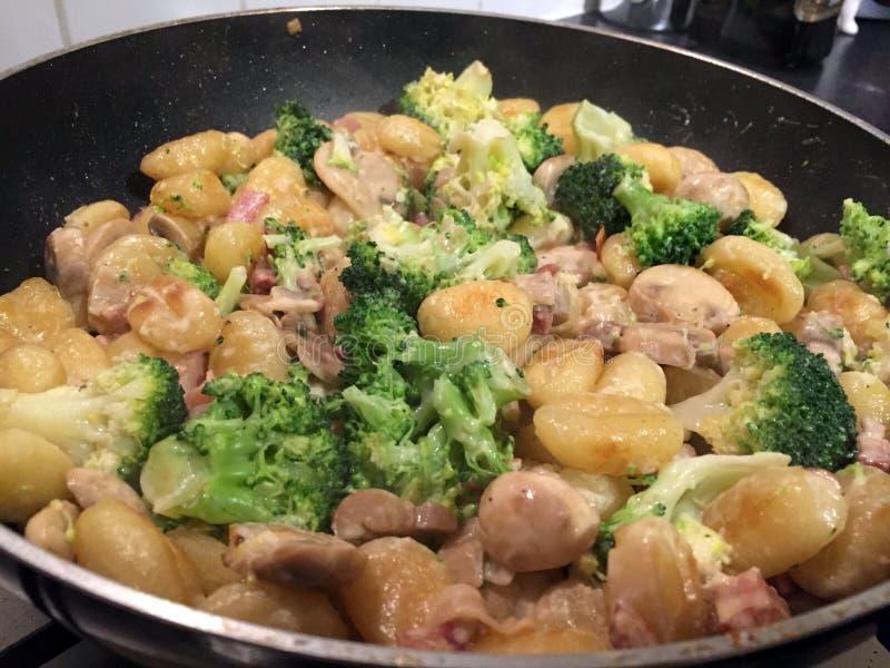Gnocchi het koken in een pan stock afbeelding