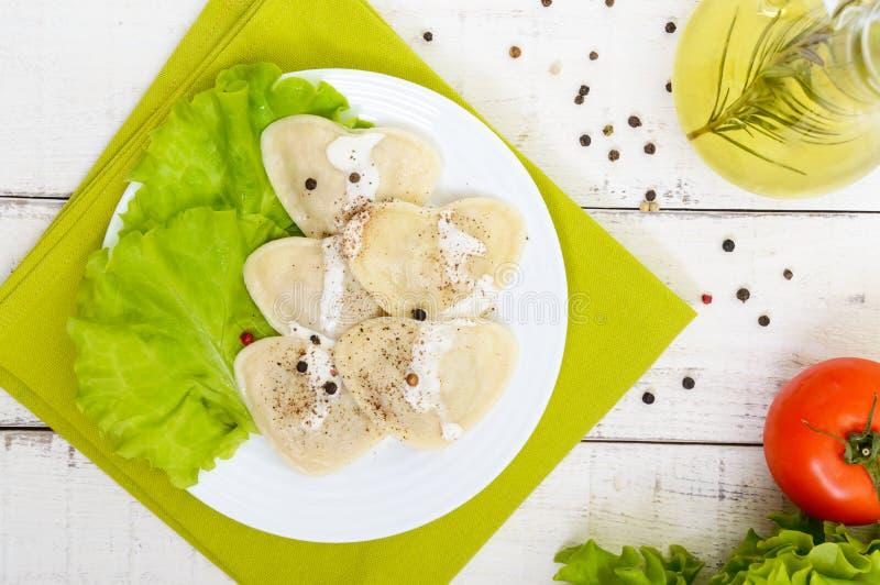 Gnocchi italiani dei ravioli sotto forma di un cuore su un piatto su fondo di legno bianco immagine stock