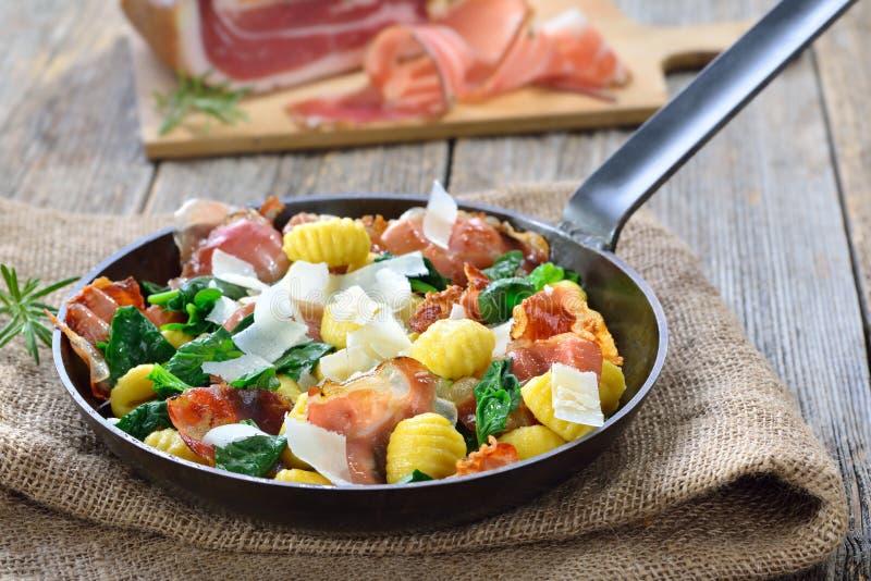 Gnocchi italiano com bacon e espinafres foto de stock