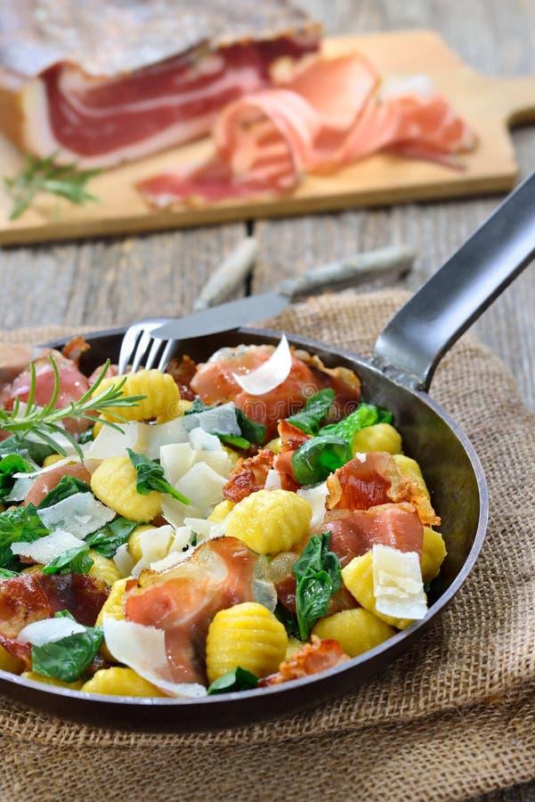 Gnocchi italiano com bacon e espinafres fotografia de stock
