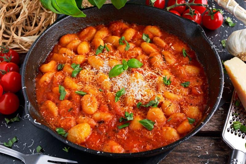 Gnocchi italien fait maison avec de la sauce à marinara, fromage dans la casserole de fer photos libres de droits