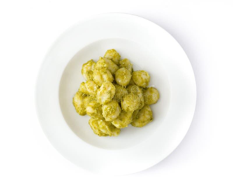 Gnocchi med pestosås i den isolerade plattan Top beskådar royaltyfri bild