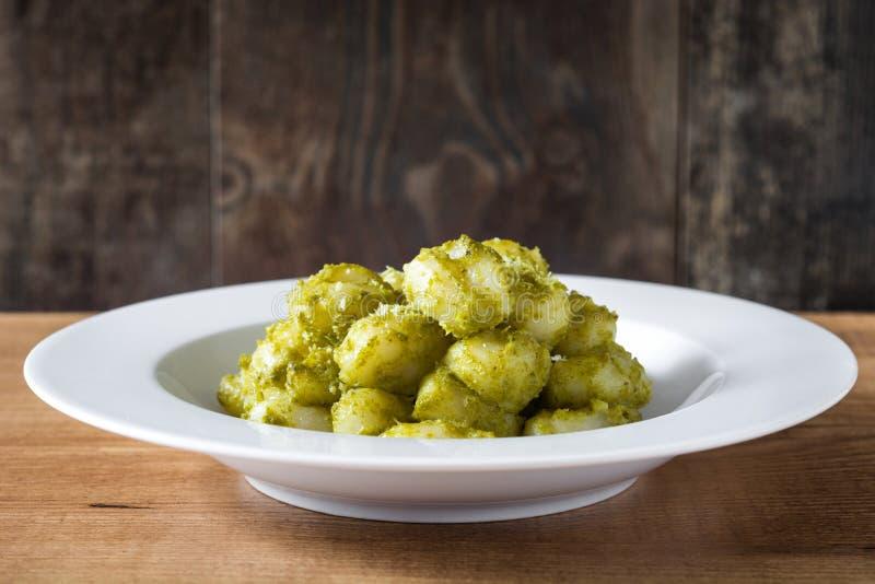 Gnocchi med pestosås i platta på trätabellen Top beskådar fotografering för bildbyråer