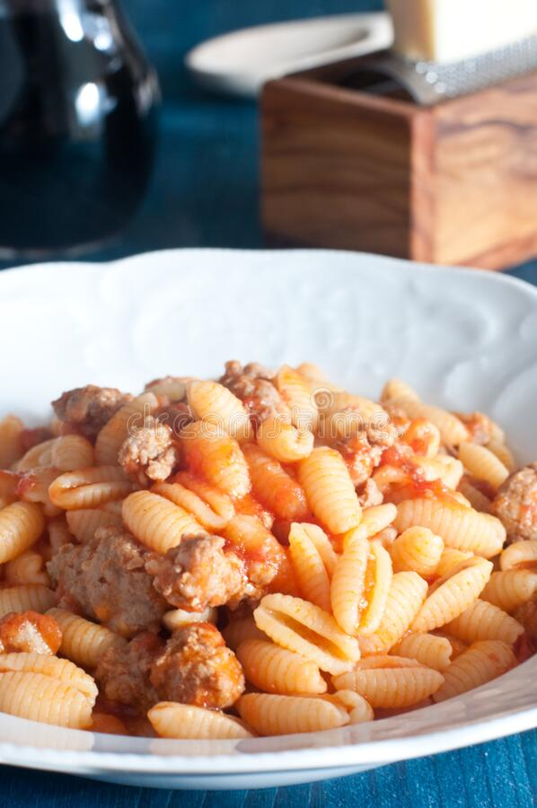 Gnocchi sardi, Malloreddus, con pomodoro e salsiccia immagini stock