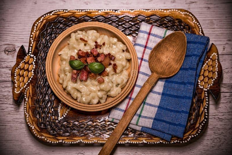 Gnocchi tradicional eslovaco de la patata de los platos con queso del ` s de las ovejas, en una tabla de madera puesta en la tabl fotografía de archivo