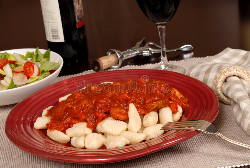 Gnocchi van de aardappel met marinarasaus met een salade en een wijn royalty-vrije stock foto's