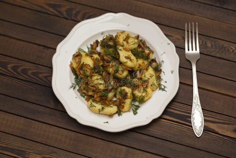 Gnocchi z pieczarkowym kumberlandem świeżymi ziele na białym talerzu i zdjęcie royalty free