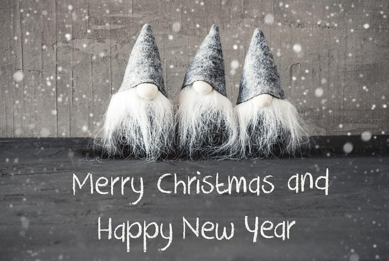 Gnomes, Cement, Snowflakes, Merry Christmas And Happy New Year. Three Gray Gnomes With English Text Merry Christmas And Happy New Year. Urban Cement Background royalty free stock photo