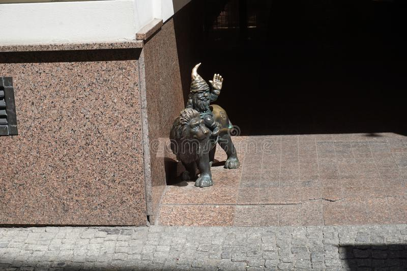 Gnomes on the streets of Wrocław. Gnome riding a lion. One of many gnomes brass figurines you can meet on the streets of Wroclaw city in Poland royalty free stock photo