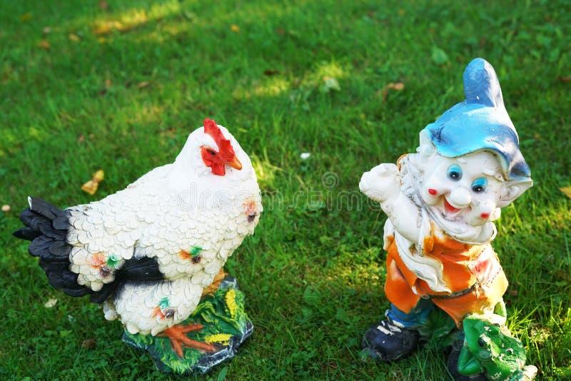 Gnomo decorativo y pollo en el jardín imagenes de archivo