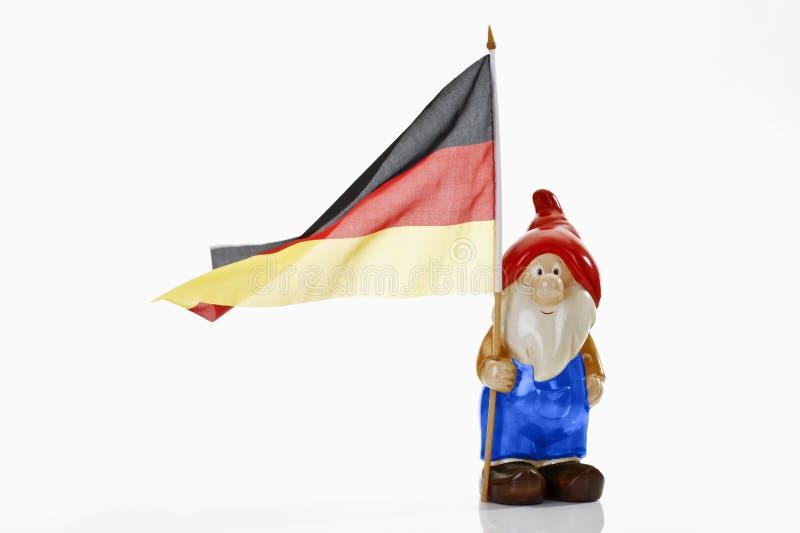 Gnomo del jardín y bandera alemana en el fondo blanco imagen de archivo libre de regalías
