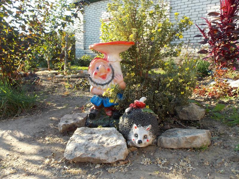 Gnomo engraçado no jardim na casa de campo imagem de stock