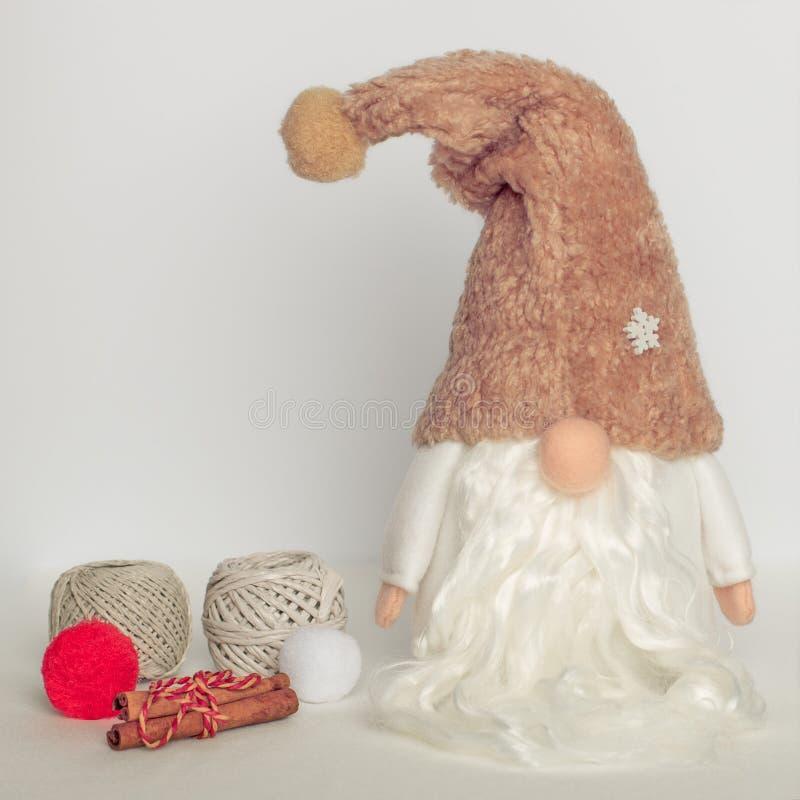 Gnomo na roupa branca e em um chapéu morno com bolas de lãs em um fundo branco imagens de stock royalty free