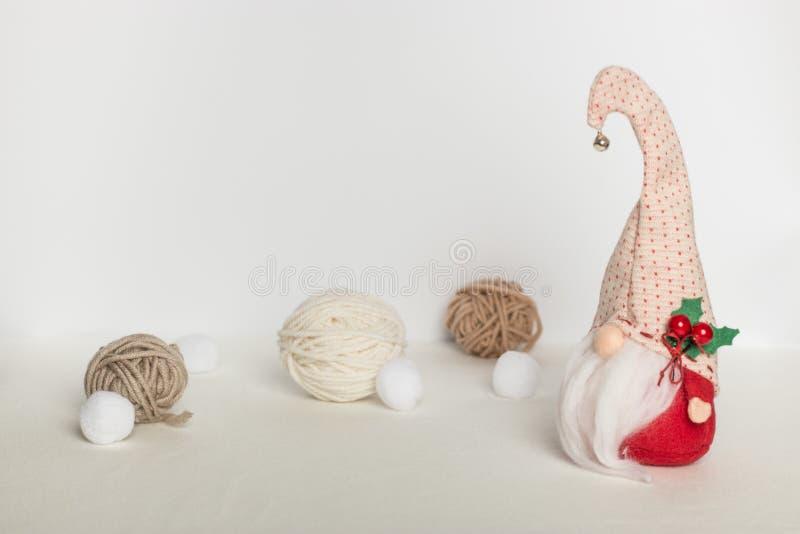 Gnomo sueco escandinavo na roupa vermelha e em um chapéu com um sino com bolas de lãs em um fundo branco imagem de stock