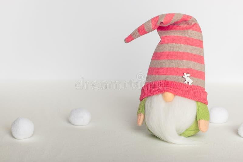 Gnomo sueco na roupa verde e no chapéu cor-de-rosa em um fundo branco imagens de stock royalty free