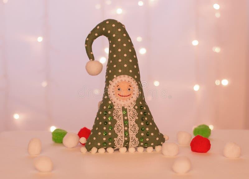 Gnomo verde allegro fatto a mano sui precedenti delle luci di Natale e delle palle molli fotografia stock